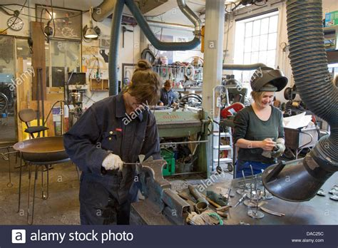 young woman working as a welder in the women's craftshop